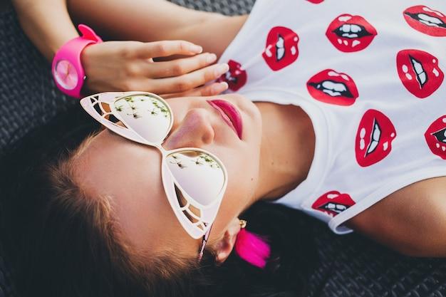 Jonge mooie hipster vrouw, liegen, zonnebril, stijlvolle outfit, zomervakantie, plezier, glimlachen, gelukkig, kleurrijk, uitzicht van bovenaf