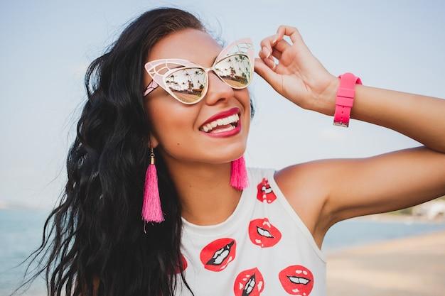 Jonge mooie hipster vrouw op tropisch strand, zonnebril, stijlvolle outfit, zomervakantie, plezier, glimlachen, gelukkig, kleurrijk, positieve emotie, accessoires