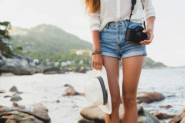 Jonge mooie hipster vrouw op zomervakantie, azië, ontspannen op tropisch strand, digitale fotocamera, casual boho-stijl, zee landschap, slank gebruind lichaam, alleen reizen, close-up detailaccessoires