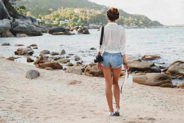 Jonge mooie hipster vrouw op zomervakantie in azië, ontspannen op tropisch strand, digitale fotocamera, casual boho-stijl, zee landschap, slank gebruind lichaam, alleen reizen, vrijheid