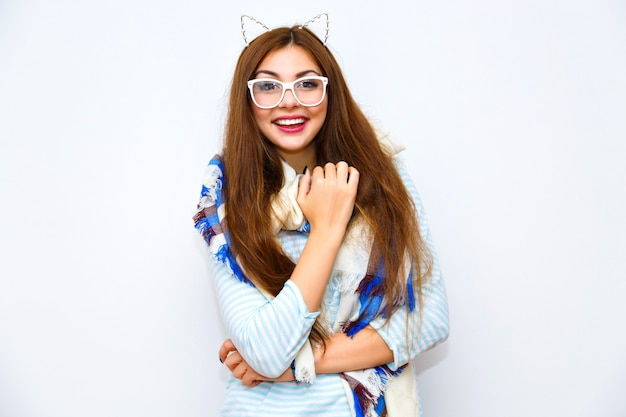 Jonge mooie hipster vrouw poseren tegen witte muur, glimlachend met plezier, lange haren lichte make-up, grote gezellige sjaal en grappige partij kat oren. felle kleuren, vreugde, positief, wintertijd.