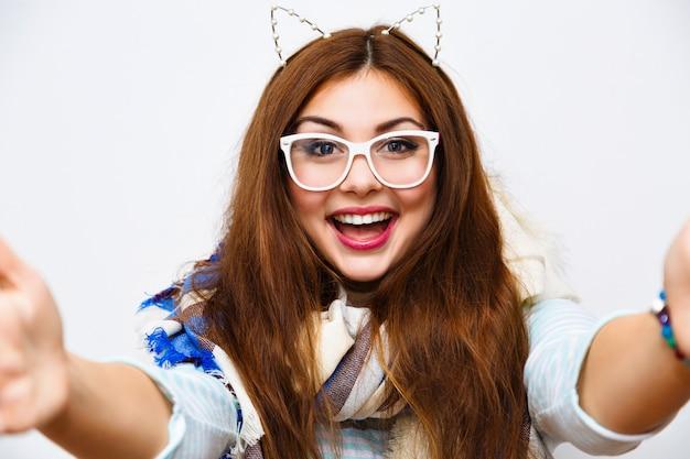 Jonge mooie hipster vrouw selfie maken tegen witte muur, glimlachend met plezier, lange haren lichte make-up, grote gezellige sjaal en grappige partij kat oren.
