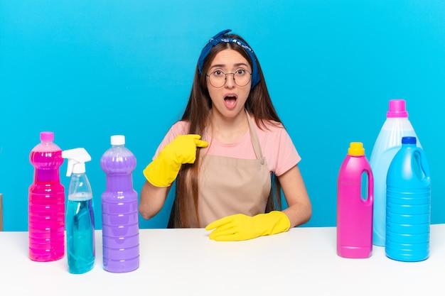 Jonge mooie huishoudster die geschokt en verrast kijkt met wijd open mond