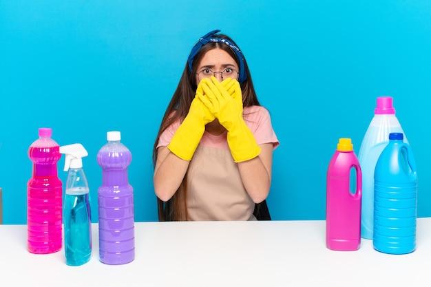 Jonge mooie huishoudster die mond bedekt met handen met een geschokte, verbaasde uitdrukking, een geheim houdt of oeps zegt saying