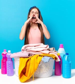 Jonge mooie huishoudster die zich gelukkig, opgewonden en positief voelt, een grote schreeuw geeft met de handen naast de mond, roept calling