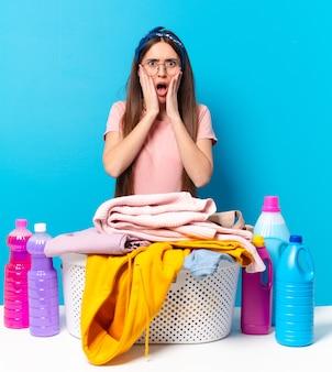 Jonge mooie huishoudster die zich geschokt en bang voelt, doodsbang kijkt met open mond en handen op de wangen