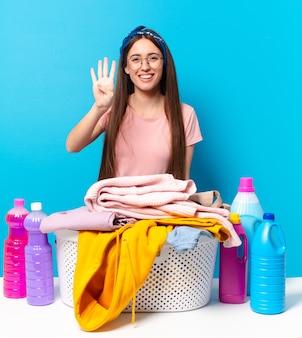 Jonge mooie huishoudster glimlachend en vriendelijk kijkend, nummer vier of vierde tonend met de hand naar voren, aftellend