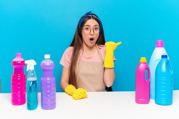 Jonge mooie huishoudster kijkt verbaasd in ongeloof, wijst naar een object aan de zijkant en zegt wow, ongelooflijk unbeliev