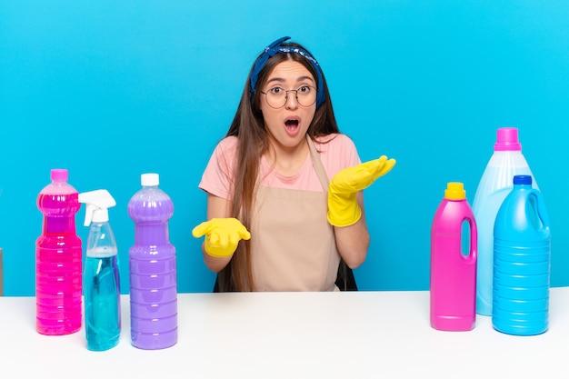Jonge mooie huishoudster met open mond en verbaasd, geschokt en verbaasd over een ongelooflijke verrassing