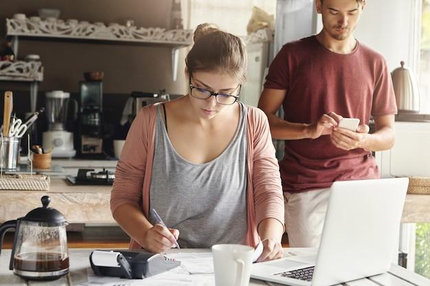 Jonge mooie huisvrouw die een rechthoekige bril draagt die noodzakelijke berekeningen maakt en met pen opschrijft, terwijl het betalen van energierekeningen, zittend aan keukentafel met generieke laptop en calculator