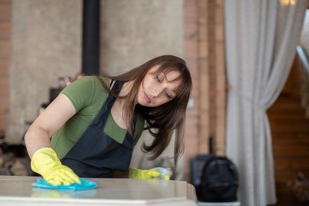 Jonge mooie huisvrouw die in gele rubberhandschoenen huis schoonmaken