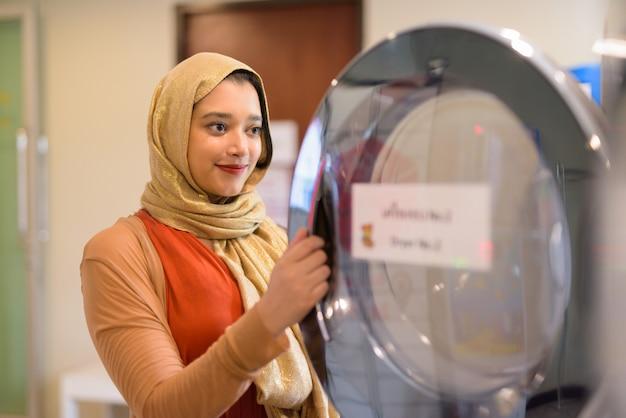 Jonge mooie indiase moslim vrouw wasserij in de droger controleren
