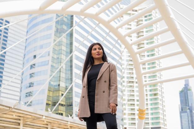 Jonge mooie indiase onderneemster die bij de skywalk-brug denken