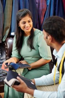 Jonge, mooie indiase vrouw die de stoffencatalogus controleert wanneer ze praat met een kleermaker in het atelier en een maatpak bestelt