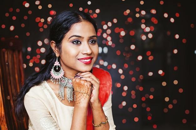 Jonge mooie indiase vrouw die sieraden en feestelijke etnische kleding draagt