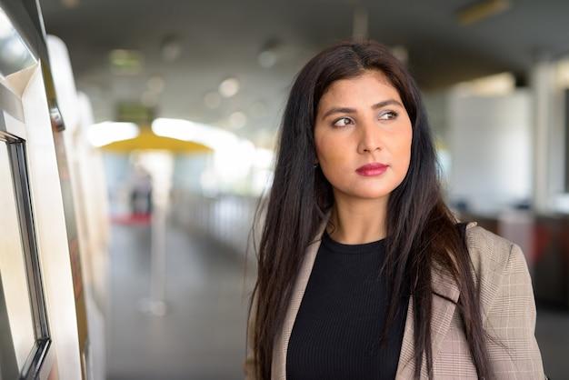 Jonge mooie indiase zakenvrouw denken bij het skytrain-station