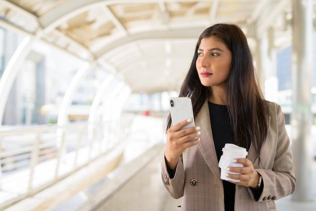 Jonge mooie indiase zakenvrouw denken tijdens het gebruik van telefoon en koffie onderweg in de stad