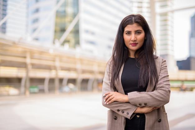 Jonge mooie indiase zakenvrouw met armen gekruist op de skywalk-brug