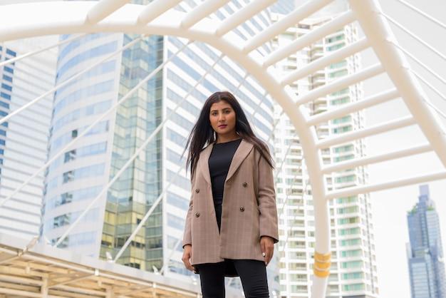 Jonge mooie indiase zakenvrouw op de skywalk-brug