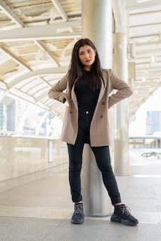 Jonge mooie indiase zakenvrouw op loopbrug in de stad