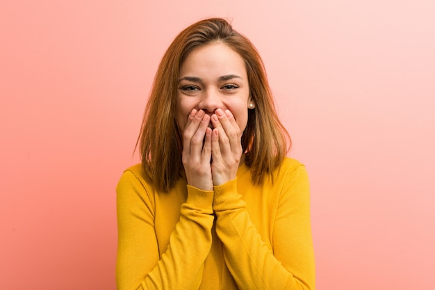 Jonge mooie jonge vrouw die om iets lacht, die mond behandelt met handen.
