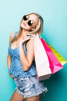Jonge mooie jonge vrouw met gekleurde boodschappentassen op blauwe achtergrond