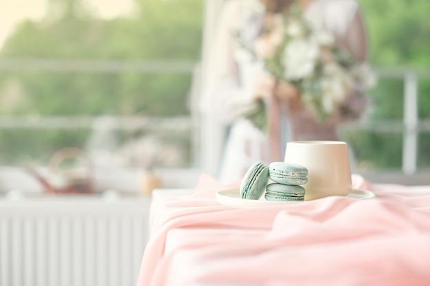 Jonge mooie kaukasische bruid genieten van ontbijt van franse bitterkoekjes en koffie op een houten tafel met een roze chiffon tafelkleed en een vaas met bloemen