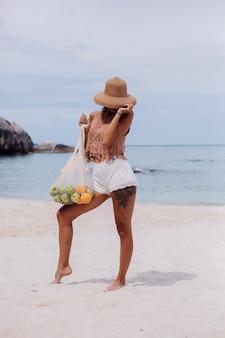 Jonge mooie kaukasische gelooide fit vrouw in gebreide kleding op tropisch strand dragen strooien hoed bedrijf ecologie herbruikbare tekenreeks tas vol fruit apple oranje druiven