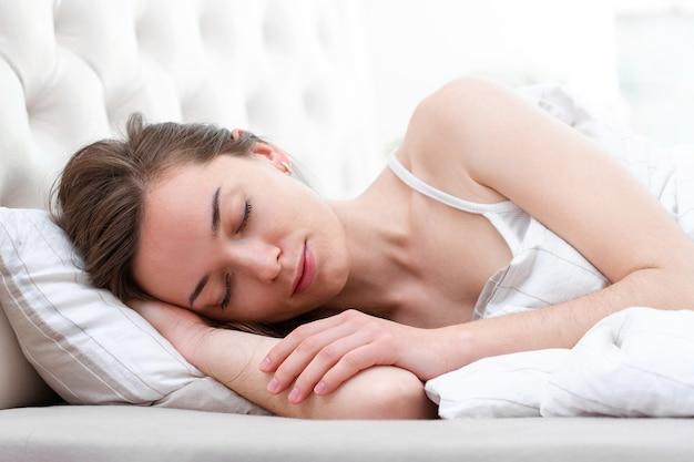 Jonge mooie kaukasische vrouw bedekt met een deken slapen en ontspannen op het kussen in bed in de vroege ochtend