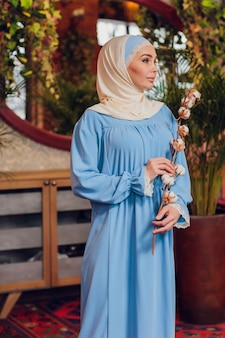 Jonge mooie kaukasische vrouw die traditionele moslimhoofddoek draagt in hipster coffeeshop met grote vensters van volledige lengte. vrouw in blauwe hijab in gezellig café. achtergrond, kopieer ruimte, close-up portret.