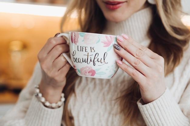 Jonge mooie kaukasische vrouw met lang kastanjebruin haar in witte trui houdt een witte kop koffie of thee, drinkt het en geniet van haar leven