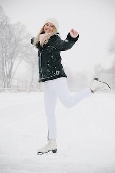 Jonge mooie kaukasische vrouw schaatsen op de ijsbaan