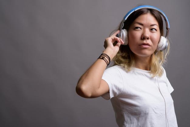 Jonge mooie kazachse vrouw die aan muziek tegen grijze muur luistert
