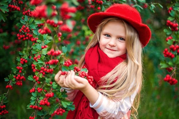 Jonge mooie kleine stijlvolle meisje in een zonnige herfst park