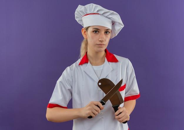 Jonge mooie kok in chef-kok het eenvormige mes en hakmes kijken Gratis Foto