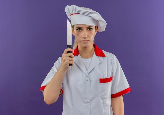 Jonge mooie kok in chef-kok het eenvormige mes houden en het kijken
