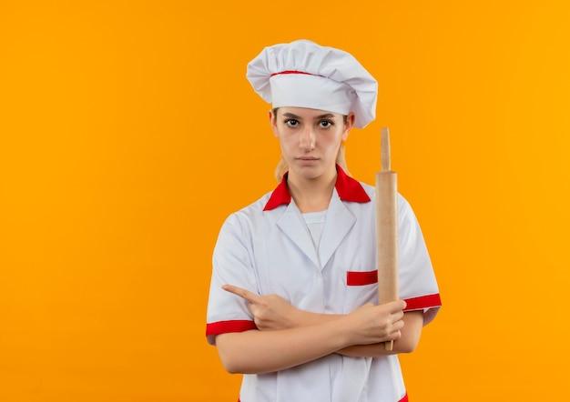 Jonge mooie kok in de deegrol van de chef-kok de eenvormige holding en wijst naar kant