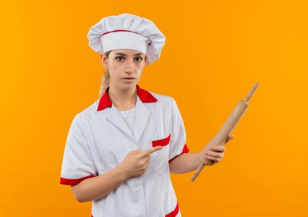 Jonge mooie kok in de deegrol van de chef-kok eenvormige holding