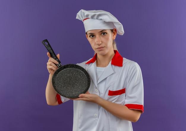 Jonge mooie kok in de koekenpan van de chef-kok het eenvormige bedrijf kijken