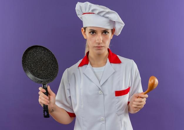 Jonge mooie kok in de pan en de lepel van de chef-kok het eenvormige bedrijf het kijken