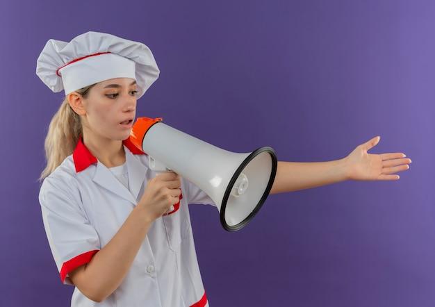 Jonge mooie kok in eenvormige chef-kok die zich uit hand aan zij uitstrekt en door spreker spreekt