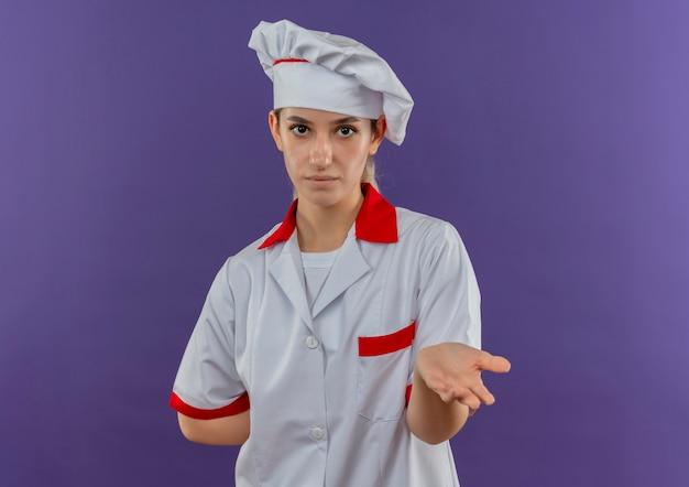 Jonge mooie kok in eenvormige chef-kok met lege hand zetten een andere hand achter haar rug en kijken