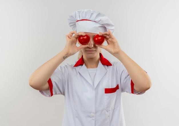 Jonge mooie kok in uniforme chef-kok tomaten op ogen zetten