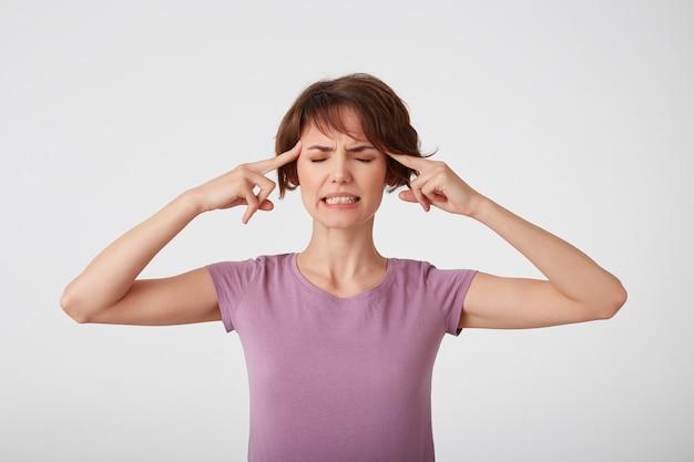 Jonge mooie kortharige dame in een leeg t-shirt, lijdt aan migraine, kan geen pijn vasthouden, raakt slapen aan, klemt tanden op elkaar, voelt zich ongemak geïsoleerd over een witte muur.