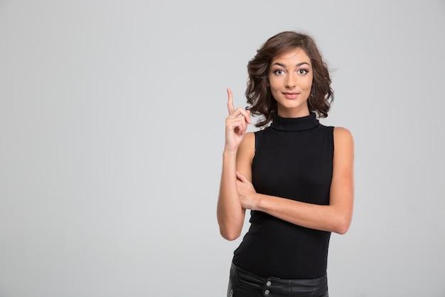 Jonge mooie krullend geïnspireerde vrouw in zwarte kleding die met haar vinger naar boven wijst en een idee heeft