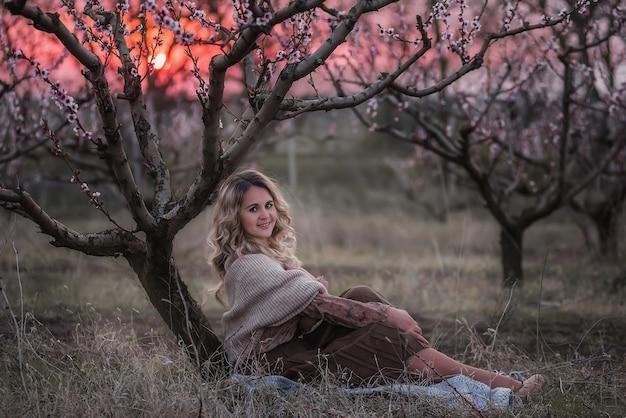 Jonge mooie krullende blonde vrouw in bruin geplooide rok, roze blouse, bedekt schouders met gebreide sjaal, zit in bloeiende perzik zonsondergang tuinen
