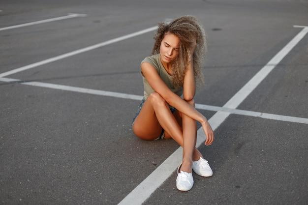 Jonge mooie krullende vrouw in modieuze denim shorts en een tanktop met witte sneakers zit en rusten op het asfalt