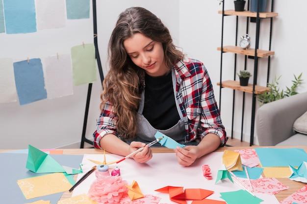 Jonge mooie kunstenaarsvrouw die origamivissen schildert die penseel gebruiken