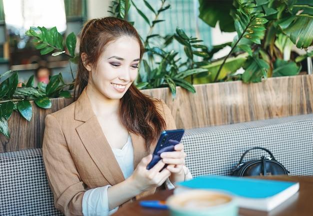 Jonge mooie lachende aziatische studente in beige pak met behulp van mobiele telefoon op groen café