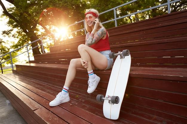 Jonge mooie lachende blonde vrouw met getatoeëerde armen, in gesprek met zijn vriendje op smartphone, wachtend op datum. draagt in een rood t-shirt, een spijkerbroek, met een gebreide bandana op haar hoofd, in een rode bril.